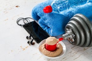 Molkenproteinpulver, ein Handtuch, Wasser, Sport und Musik führen zum Erfolg