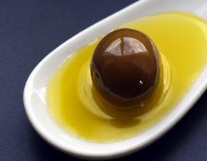 Olive in weißer Schale gefüllt mit Olivenöl