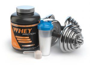 Hantel, Shaker und Whey Protein vor weißem Hintergrund